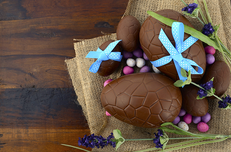 Happy Easter chocolate Easter eggs on dark wood country style ta